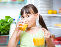 Girl drink orange juice standing near refrigerator Royalty Free Stock Photos