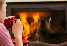 Girl with Drink Relaxing By Fireplace Stock Image