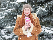Girl drink tea in winter park at day. Fir trees with snow. Stock Photo