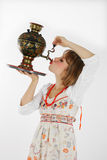 Girl drinking. From a spout samovar Royalty Free Stock Images