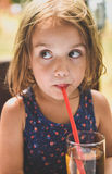 Girl drinking apple juice with a straw Royalty Free Stock Photos