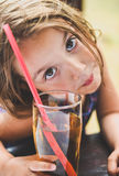 Girl drinking apple juice with a straw Stock Image