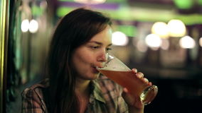 Girl drinking beer at bar stock footage