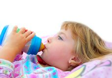 Girl drinking bottle of milk laying on bed Stock Photography
