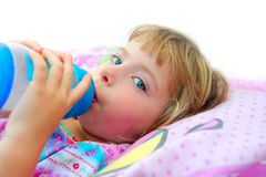 Girl drinking bottle of milk laying on bed Royalty Free Stock Images