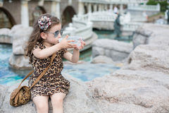 The girl is drinking from a bottle while sitting on a rock. Next to a fountain royalty free stock photos