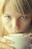 Girl drinking cappuccino Royalty Free Stock Photos