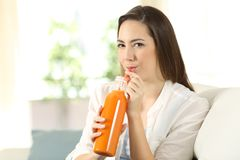 Girl drinking a carrot or orange juice from a bottle. Sitting on a couch in the living room at home Royalty Free Stock Image