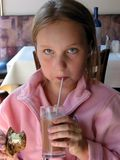 Girl drinking chocolate milk. Young girl in a cafe drinking chocolate milk Stock Images