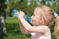 Girl is drinking clean water from a bottle royalty free stock photography
