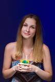Girl drinking a cocktail against blue background Stock Images