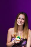 Girl drinking a cocktail against violet background Royalty Free Stock Image