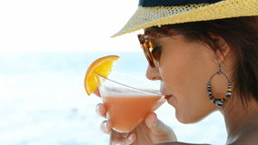 Girl Drinking Cocktail At Sea. Closeup Of Young Woman Wearing Hat And Sunglasses Holding Cocktail Glass At Seaside. Portrait of beautiful girl relaxing on the stock video