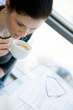 Girl drinking cofee on a transparent table Royalty Free Stock Photos