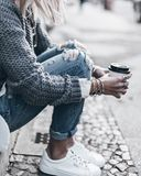 Girl in jeans drinking coffee royalty free stock photography