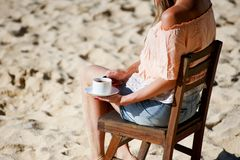 Girl drinking coffee on beach Royalty Free Stock Photo