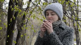 Girl is drinking coffee by a blossom tree. Wet snow.  stock footage