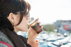The girl is drinking coffee on a blurry bokeh background