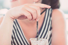 Girl drinking coffee at coffee bar. Girl drinking ice coffee by straws at coffee bar at Kolbotn, Norway Royalty Free Stock Images