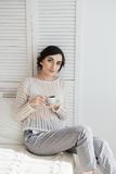 Girl drinking coffee and a croissant in bed. Young beautiful girl drinking coffee and a croissant in bed for Breakfast in the morning Stock Photography