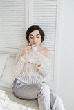 Girl drinking coffee and a croissant in bed. Young beautiful girl drinking coffee and a croissant in bed for Breakfast in the morning Royalty Free Stock Photography