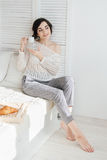 Girl drinking coffee and a croissant in bed. Young beautiful girl drinking coffee and a croissant in bed for Breakfast in the morning Stock Photos