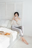 Girl drinking coffee and a croissant in bed. Young beautiful girl drinking coffee and a croissant in bed for Breakfast in the morning Stock Photo