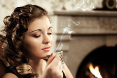Girl drinking coffee by the fireplace Stock Photography
