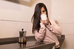Girl drinking coffee in her kitchen stock images