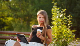 Girl drinking coffee and holding tablet pc royalty free stock photos