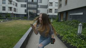 Girl drinking coffee and just have won a huge prize. She is dancing and jump. Happy excited young woman using smart phone city. Downtown. Girl won the apartment stock footage