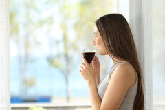 Girl drinking coffee looking through a window stock photography