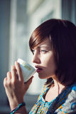 Girl drinking coffee in the morning. Toned photo Royalty Free Stock Photography