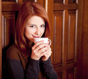 Girl drinking coffee near wood doors. Stock Photo