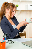 Girl is drinking coffee in the office Royalty Free Stock Images