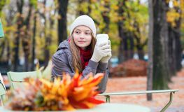 Girl drinking coffee in an outdoor cafe Stock Image