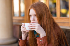 Girl drinking coffee in outdoor cafe Royalty Free Stock Images