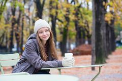 Girl drinking coffee in an outdoor cafe Stock Images