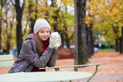Girl drinking coffee in an outdoor Parisian cafe Stock Photo