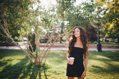 Girl drinking coffee in the park. Girl drinking coffee in a paper cup among green trees in the park Royalty Free Stock Photos