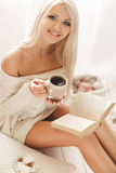 The girl is drinking coffee and reading a book Royalty Free Stock Images