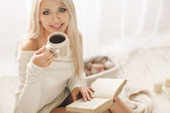 The girl is drinking coffee and reading a book Royalty Free Stock Photos