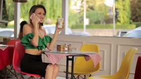 Girl drinking coffee. And shows a purchase using a smartphone, a happy girl after shopping stock footage