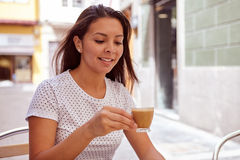 Girl drinking coffee in a street cafe Stock Photography