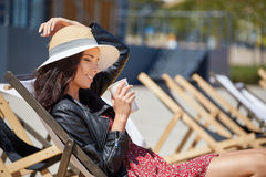 The girl is drinking coffee on a sun lounger on the street.  Royalty Free Stock Photos