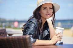 The girl is drinking coffee on a sun lounger on the street.  Royalty Free Stock Photo