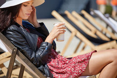 The girl is drinking coffee on a sun lounger on the street Royalty Free Stock Photos