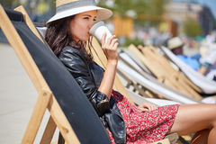 The girl is drinking coffee on a sun lounger on the street Royalty Free Stock Photography