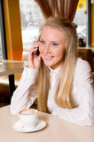 Girl drinking coffee and talking on  phone Stock Photo