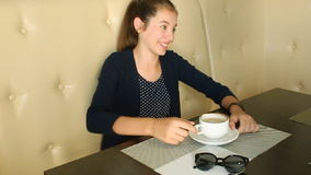 Girl drinking coffee and talking on the phone stock video